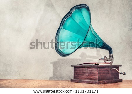 Vintage antique aged aquamarine gramophone phonograph turntable on wooden table front concrete wall background with its shadow. Retro old style filtered photo #1101731171