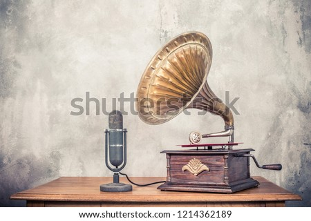 Vintage antique gramophone phonograph turntable with brass horn and big aged studio microphone on wooden table front concrete wall background. Retro old style filtered photo #1214362189