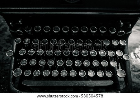 Vintage Antique Typewriter Machine Close up photo of the keys, shallow focus looks on a wooden table in black and white.