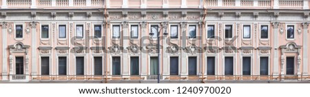 Vintage architecture is a long two-story classical facade of an elegant old building richly decorated with architectural details. Front view.