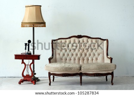 Vintage armchair with retro lamp and old day telephone