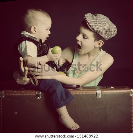 vintage art portrait of little boy eating an apple with his baby brother leaning on old suitcase, retro stylization of 30-50s