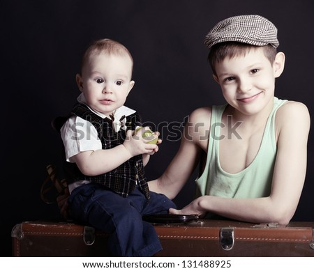 vintage art portrait of little boy with his baby brother leaning on old suitcase, retro stylization of 30-50s, toned