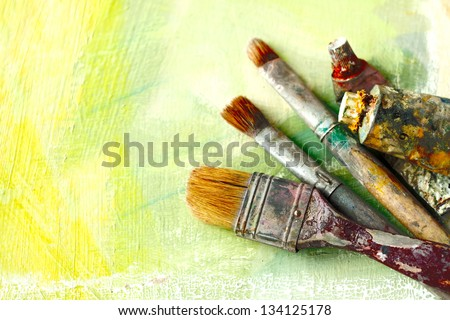 Vintage artists brushes and paint tubes on an abstract artistic background