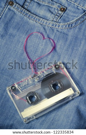 vintage audio cassette on blue jeans with red tape pulled out as heart shape