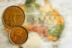 Vintage Australian penny and half-penny over blurred map.  Retro effects.