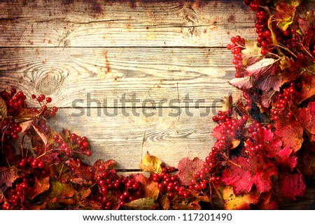 Vintage Autumn border from ashberry and and fallen leaves on old wooden table/Thanksgiving day concept/