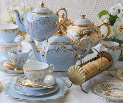 Vintage baby blue teacups and teapots with gold cutlery flatware and macaroons - tea party