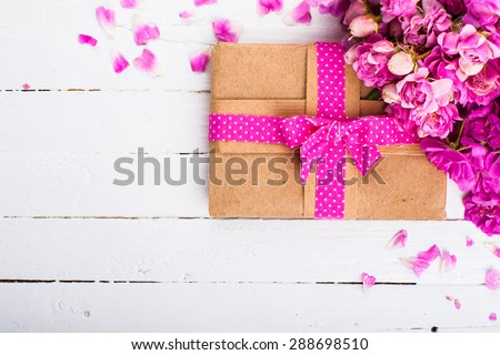 Vintage background with a gift and flowers on a wooden surface