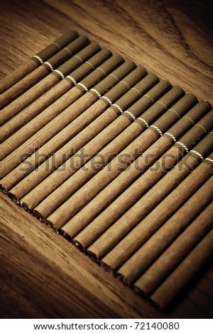 Vintage background with cigarettes on brown wooden background