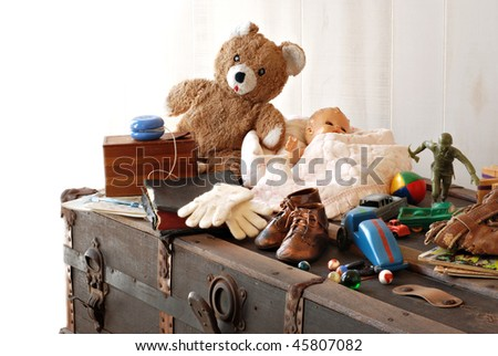 Vintage background with collection of antique childhood treasures on rustic old steamer trunk.  Fades into white background for copy space.