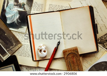 Vintage background with old note-book, books, postcards, photographs, pen, wooden pen-case and stone