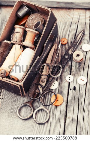 Vintage Background with sewing tools and colored tape/Sewing kit. Scissors, bobbins with thread and needles on the old wooden background #225500788