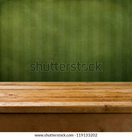 Vintage background with wooden table and grunge green wall