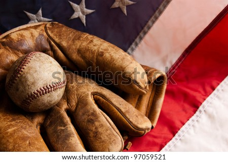 Vintage baseball and glove on American flag