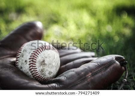 Vintage baseball glove and ball on grass. Very shallow focus on stitching
