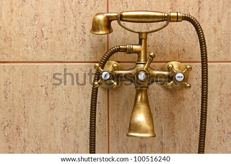 Vintage bathtub faucet and ceramic tiles in background.Retro bronze look.