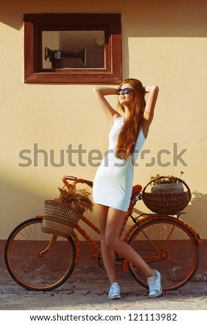 Vintage beautiful fashion girl with bicycle in the morning - stock photo