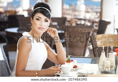 vintage beautiful woman in restaurant cafe with tiramisu cake and coffee.Healthy food  drink for breakfast.Stylish rich slim girl in retro dress.glamorous lady at vacation. Retro style.France.series