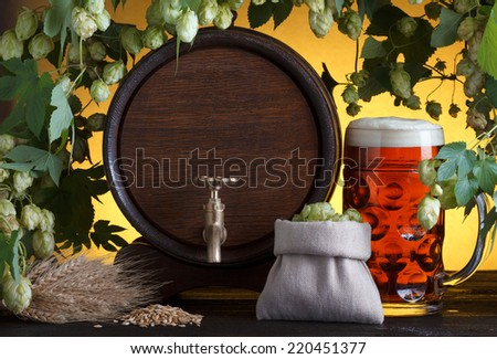 Vintage beer barrel with beer glass and fresh hops, with barley on wooden table still life