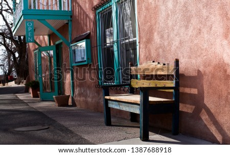 Vintage bench outside adobe house on quiet town street in Taos, New Mexico