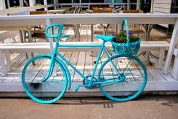 Vintage bicycle bike, flower basket. Cycle vintage bike in blue aqua color, flowers bicycle. Vintage retro style design of summer terrace cafe - retro bicycle, wicker flower basket. Cafe interior