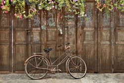 Vintage bicycle in front of the old rustic house, covering with the flower on the roof and many text on the wall. Classic bike and old house decorated perfectly look like retro style