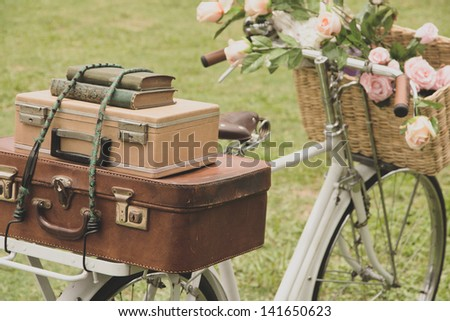 Vintage bicycle on the field with a bag and basket