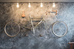 Vintage Bicycle on the wall decorate with bike cycle wheel in living room.Interior Design with people lifestyle hobby in a modern city. Bicycle with bulb lighting as background and loft decorate style