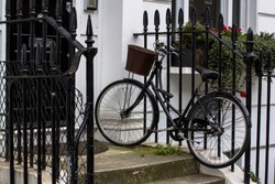 Vintage bicycle with basket on the porch. Entrance Door to residential building in London. Typical door in the English style
