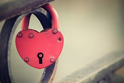 vintage  big padlock of red color is fixed in the locked state on an iron fence and has a keyhole, the digital photo with a retro effect, blank space for the text,