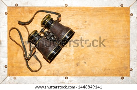 Vintage Binoculars on an edged wooden background, offset to top left, room for text. Collectable object finished in leather and brass.