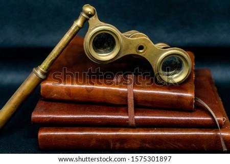 vintage binoculars on vintage notebooks #1575301897