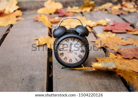 Vintage black alarm clock on autumn leaves. Time change abstract photo. Daylight saving time.
