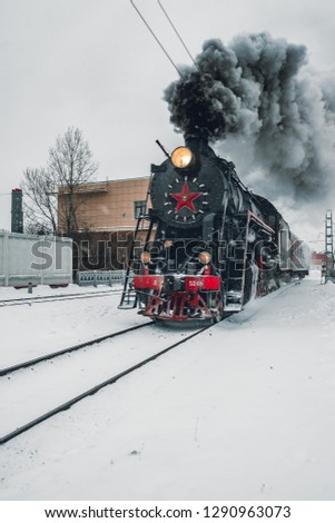 Vintage Black and Red Steam Locomotive Train in Winter. Clouds of smoke and clean white sky, snow all around