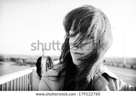 Vintage black and white photos. Love story. Portrait of beautiful girl with dark hair. Romance on the bridge, on the waterfront. Hair fly in the wind. Girl face close-up. Young man in the background