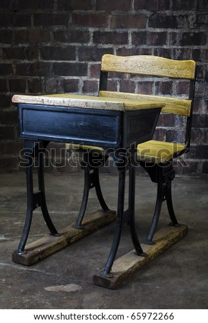 Vintage black and yellow crack paint old school desk with brick background