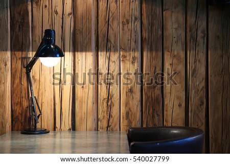 Vintage black desk lamp on wood background\Vintage background with lighting retro desk lamp on wood background