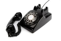 vintage  black rotary telephone with receiver off the hook isolated on a white background