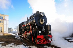 Vintage black steam locomotive. Old Soviet steam train in the depot.  Space for text. Background with steam train.