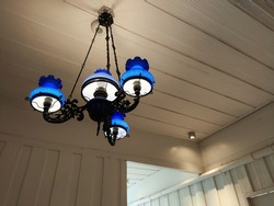 Vintage Black steel frame and blue glass chandelier in the wooden white room on low light background. Low Angle view.