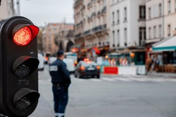 vintage black traffic red light in paris depth of field police and cars
