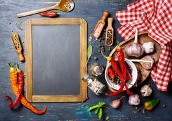Vintage blackboard and seasonings, top view. Food background concept with copyspace