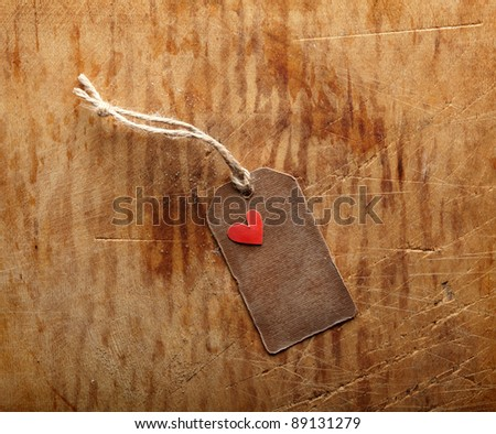 Vintage blank gift tag with small red paper heart shape on old wooden background.