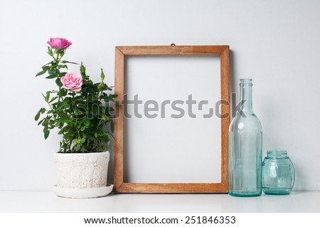 Vintage blank wooden frame, bottles and rose in a pot on a white wall #251846353