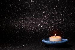 Vintage blue porcelain candle holder, burning candle on dark bokeh background, soft light. Muslim community holy month Ramadan Kareem. Greeting Festive card. Copy space. Candle making. Low key photo