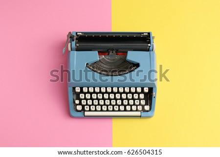 Vintage blue typewriter over a pastel background.