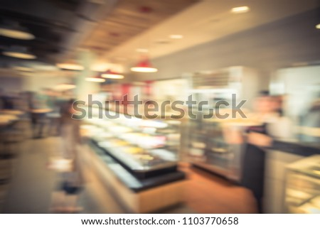 Vintage blurred diverse group of customers select cakes at from display cabinet of Asian bakery in USA. Defocused people buying fresh baked bread in pastry shop counter. Self service food concept.