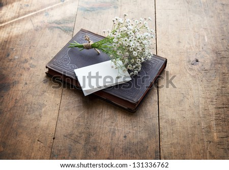 Vintage book and a small bouquet of baby's breath flowers and a blank sheet of folded white memo paper, on a well used old desk or wooden surface. - stock photo