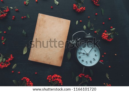Vintage book and alarm clock flat lay top view on dark wooden background decorated with wild berry fruit arrangement